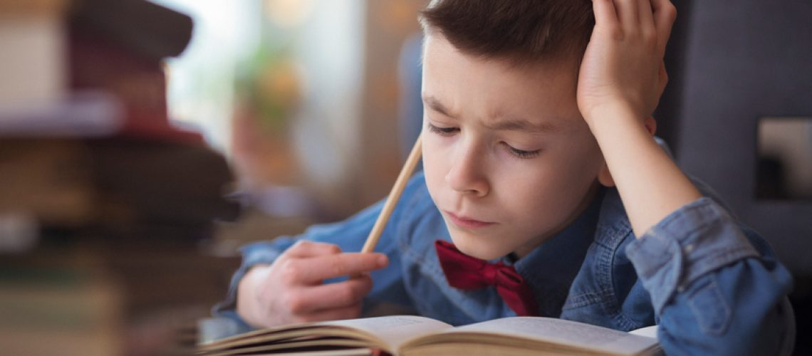 Portraits of cute little boy doing homework . Shallow DOF. Developed from RAW; retouched with special care and attention; Small amount of grain added for best final impression.16 bit Adobe RGB color profile.